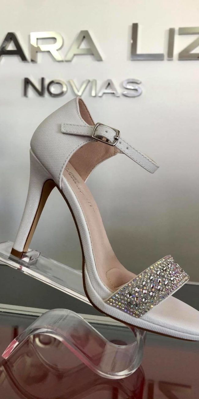 zapato blanco sobre pedestal transparente