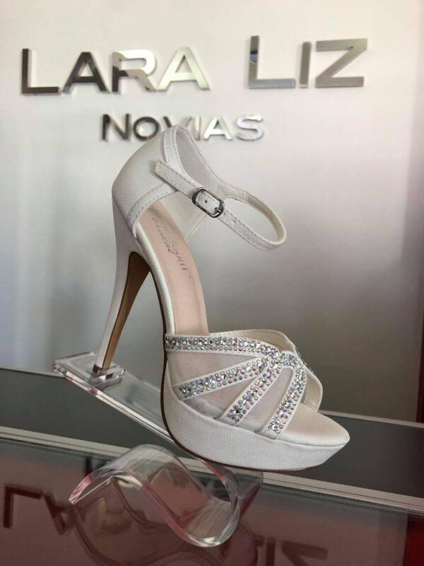Sandalia blanca en soporte transparente