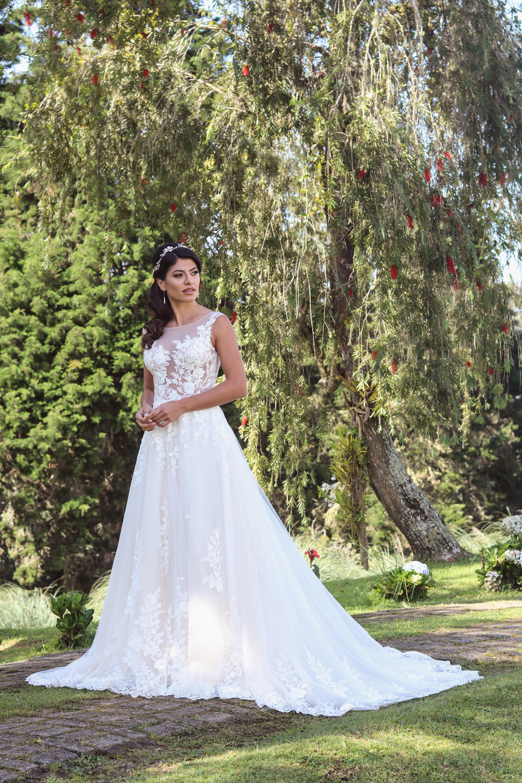 Chica morena posando en vestido de novia blanco