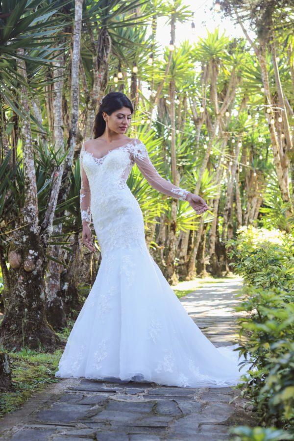 Chica morena rodeada de vegetación vestida de novia