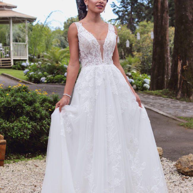 Chica guapa en vestido de novia blanco de encaje y chifón con escote